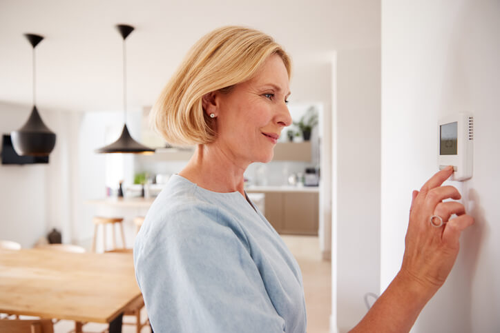 Woman Setting Up The Thermostat